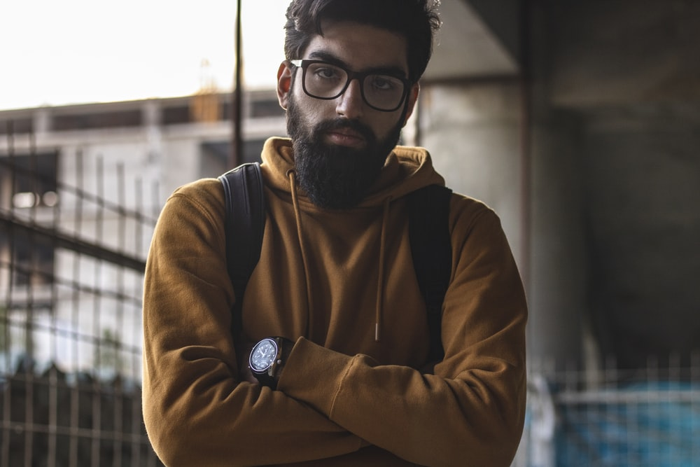 man in brown and black hoodie wearing black framed eyeglasses