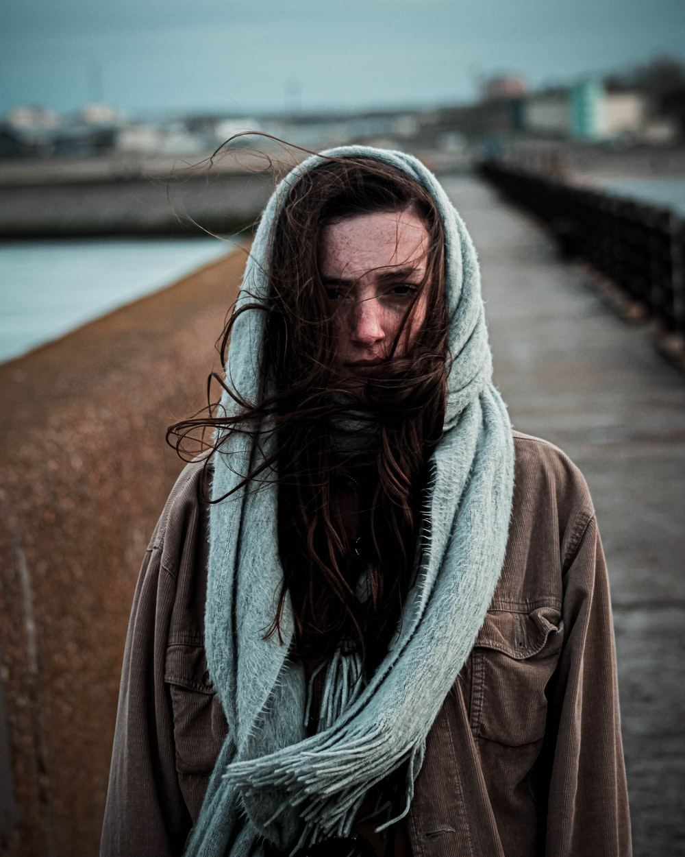woman in brown coat standing on bridge during daytime