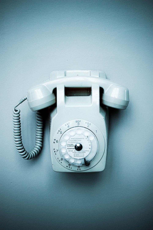 white rotary phone on white wall