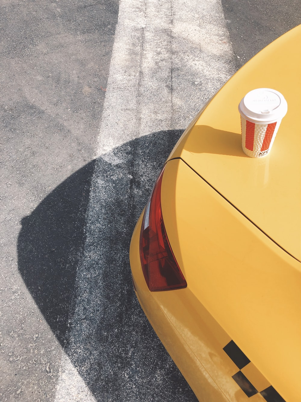 red and white disposable cup on yellow car hood