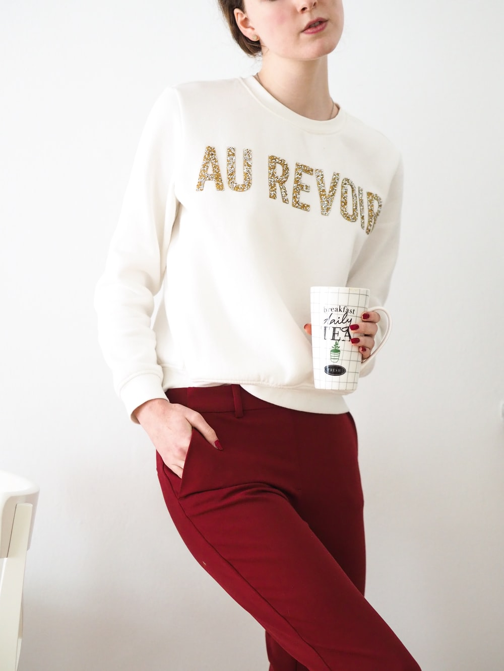 woman in white long sleeve shirt and red pants