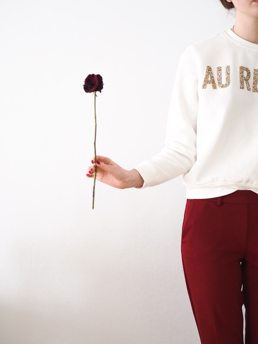 man in white sweater and red pants holding pink lollipop
