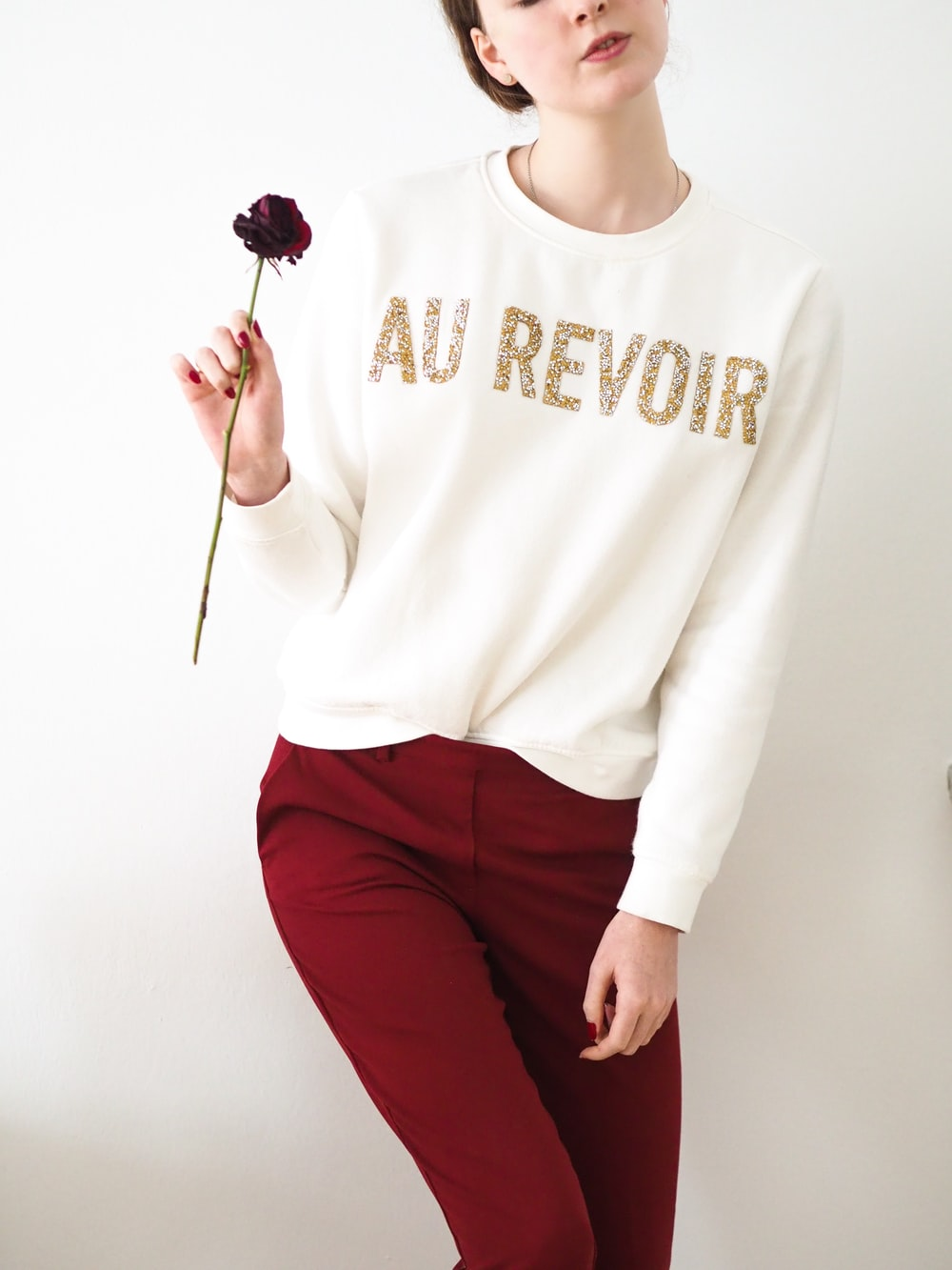 woman in white long sleeve shirt and red pants holding lollipop