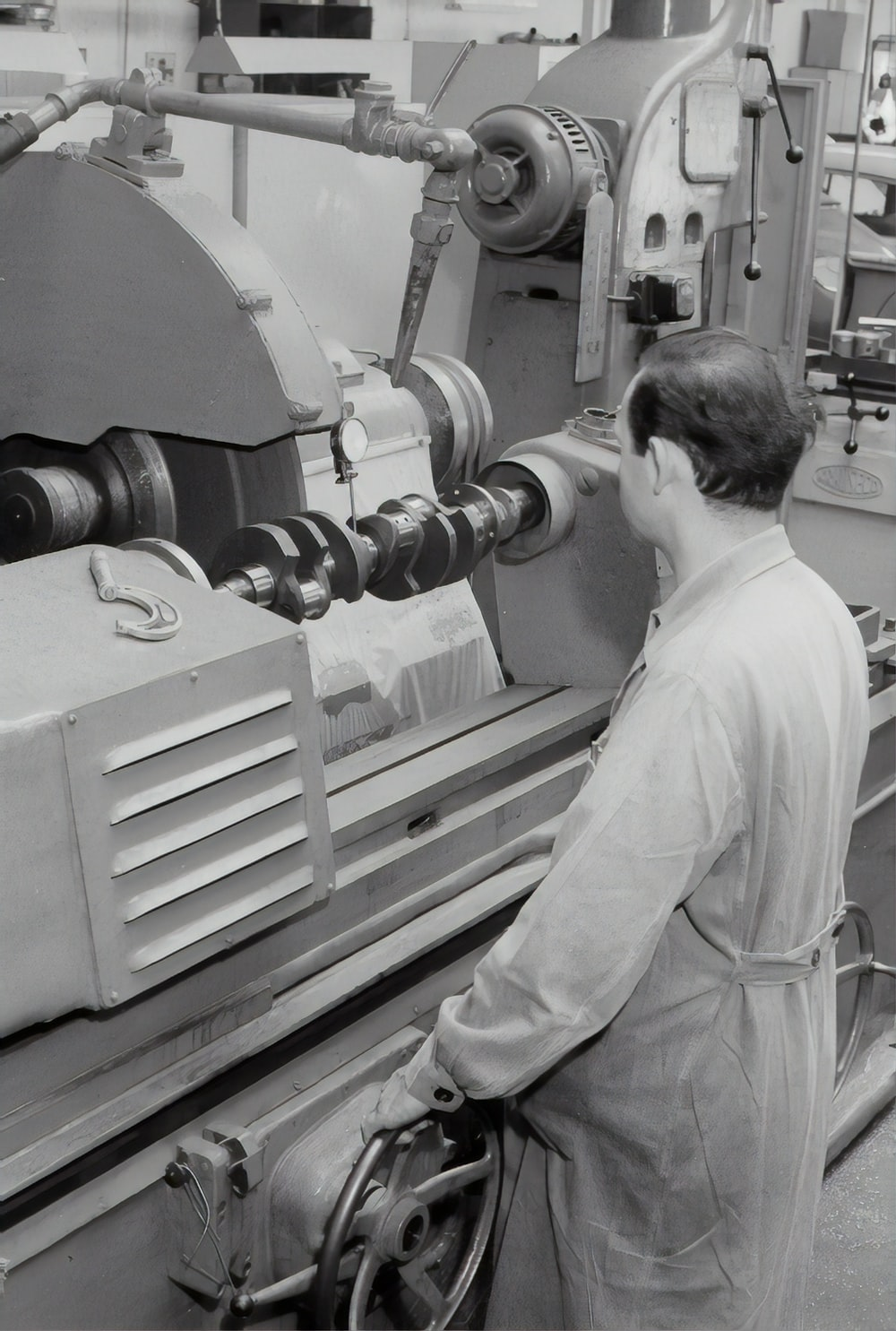 man in white shirt standing in front of white and black machine