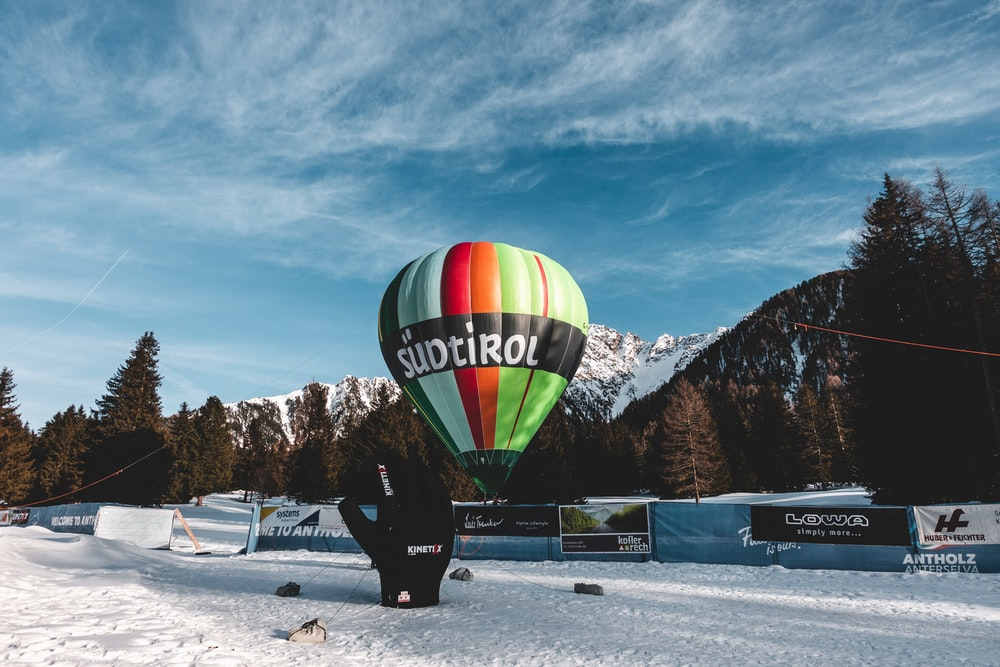 green yellow and red hot air balloon on snow covered ground during daytime