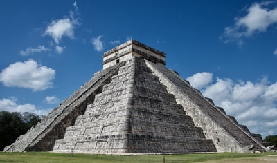 gray concrete wall on green grass field under blue sky during daytime mayan pyramid teams background
