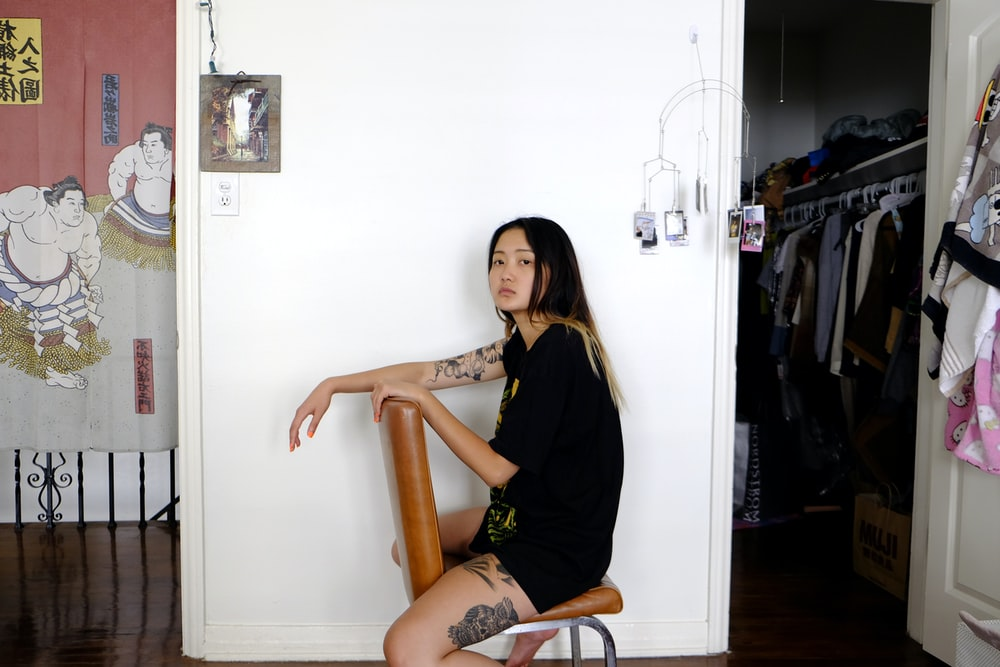woman in black long sleeve shirt sitting on brown wooden chair