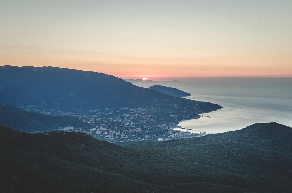 aerial view of green mountains and body of water during sunset