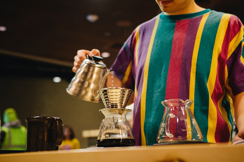 man in purple and pink striped shirt holding stainless steel coffee pot