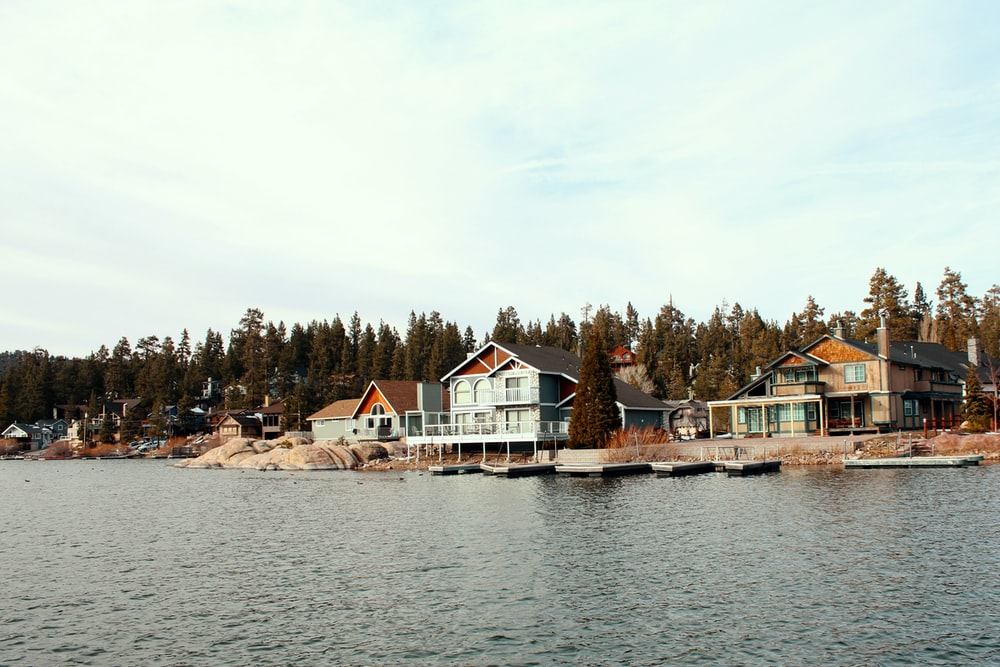 white and brown house near body of water during daytime