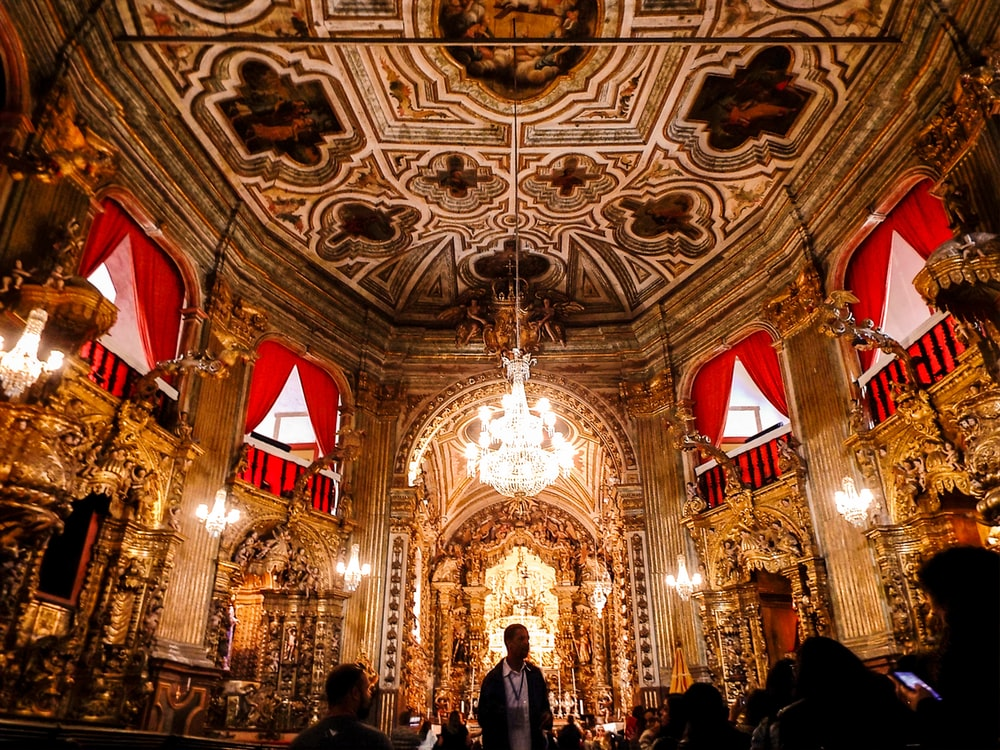 people inside cathedral with red and gold ceiling