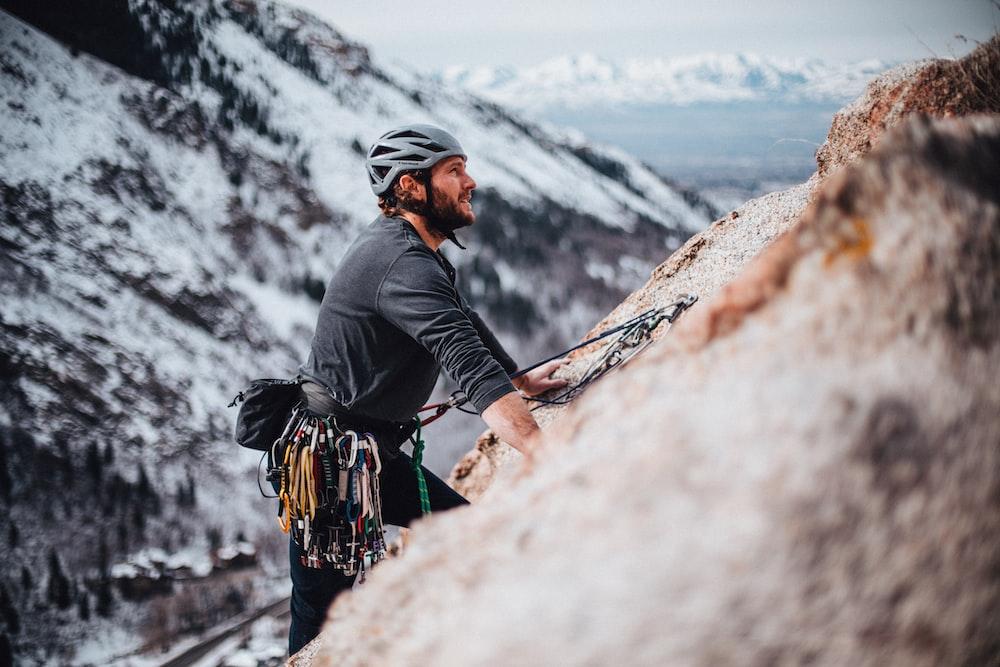 man in black jacket climbing mountain during daytime