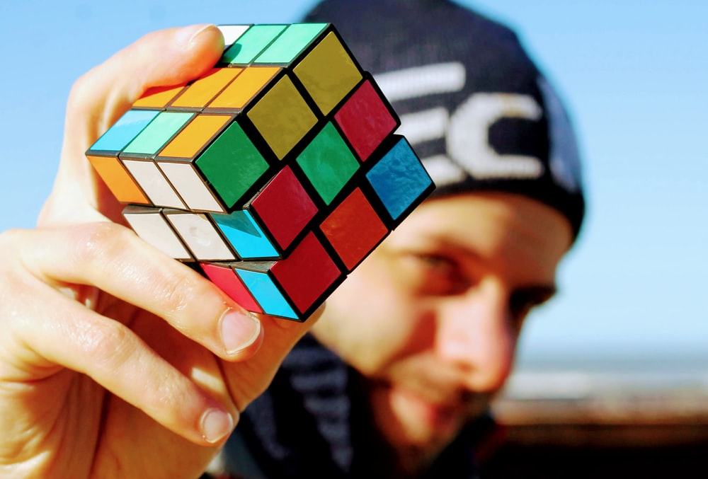 person holding 3 x 3 rubiks cube