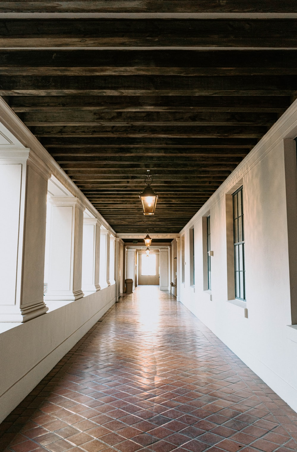 brown wooden hallway with white walls