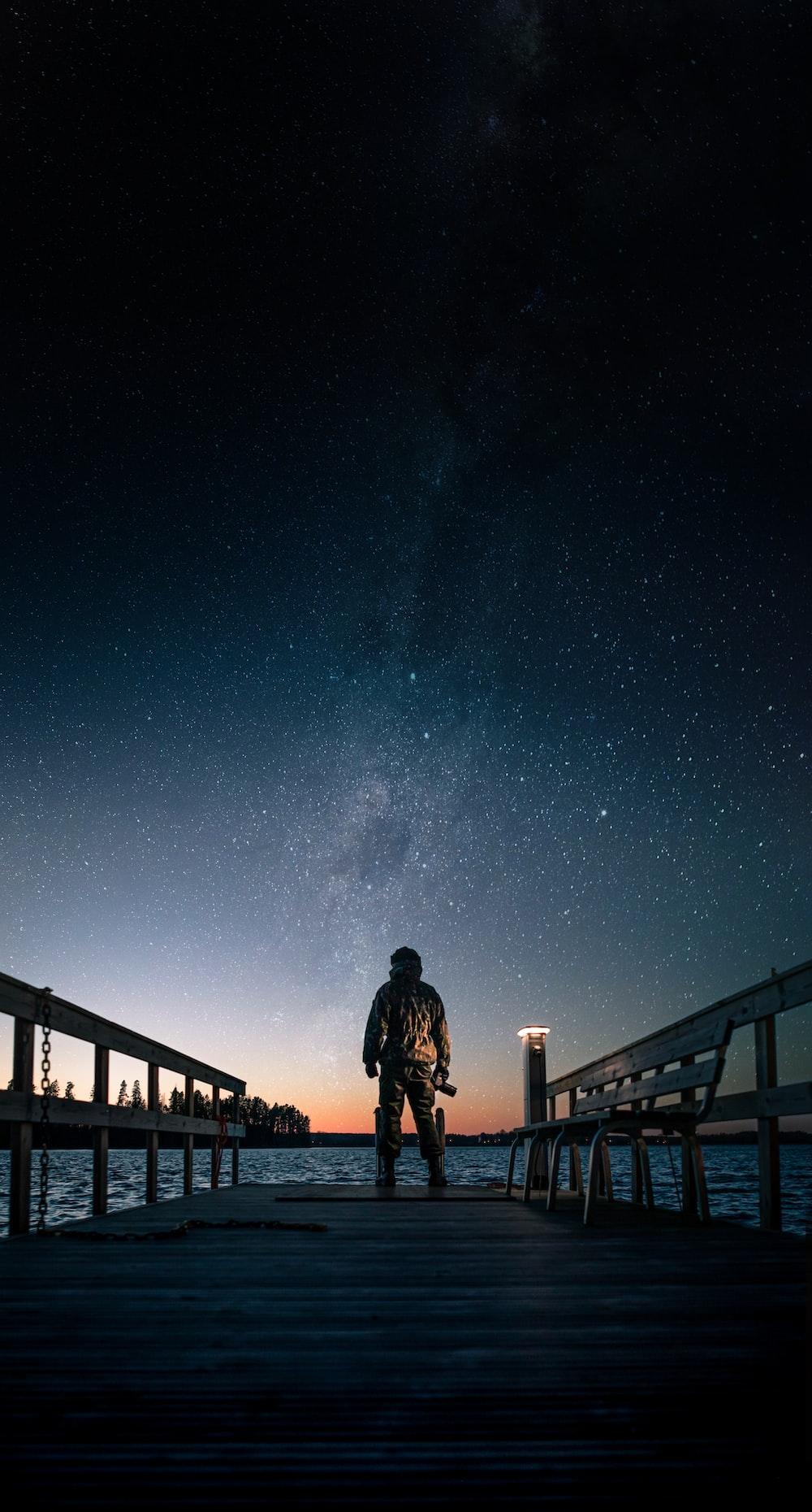 man in black jacket standing on brown wooden bridge under starry night