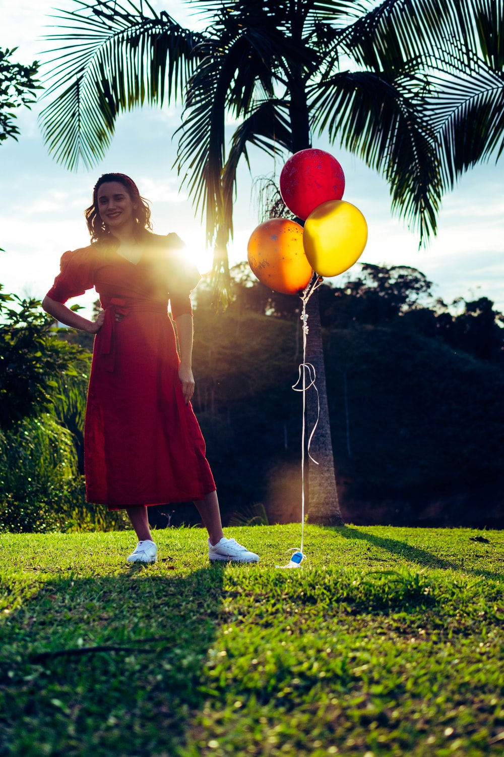 woman in red dress holding yellow balloons