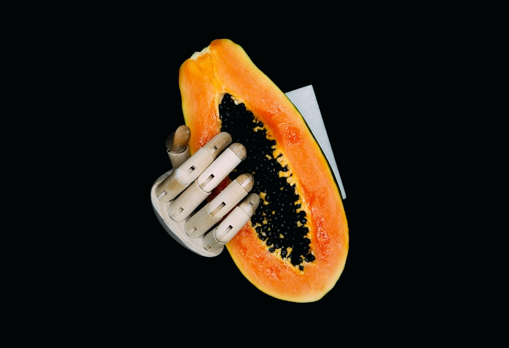 person holding orange and yellow fruit