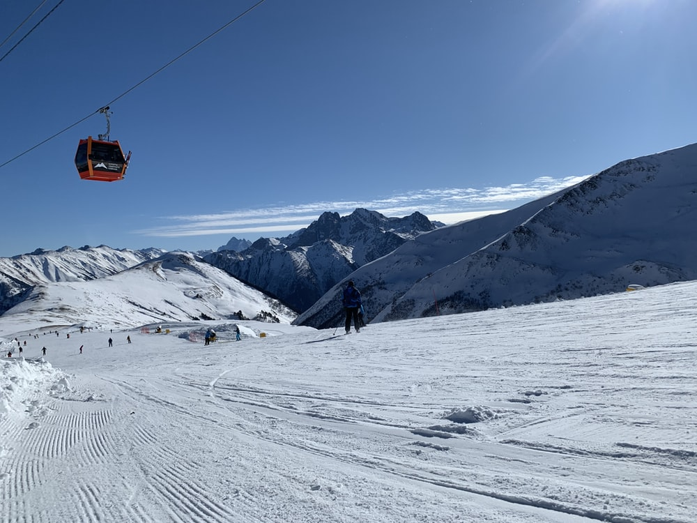 orange cable car over snow covered mountain during daytime