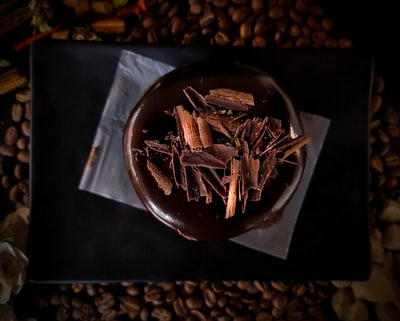 brown and white coffee beans on black paper chocolate zoom background