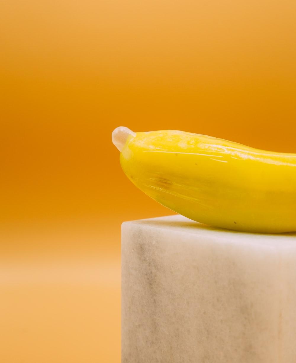 yellow banana fruit on white concrete post