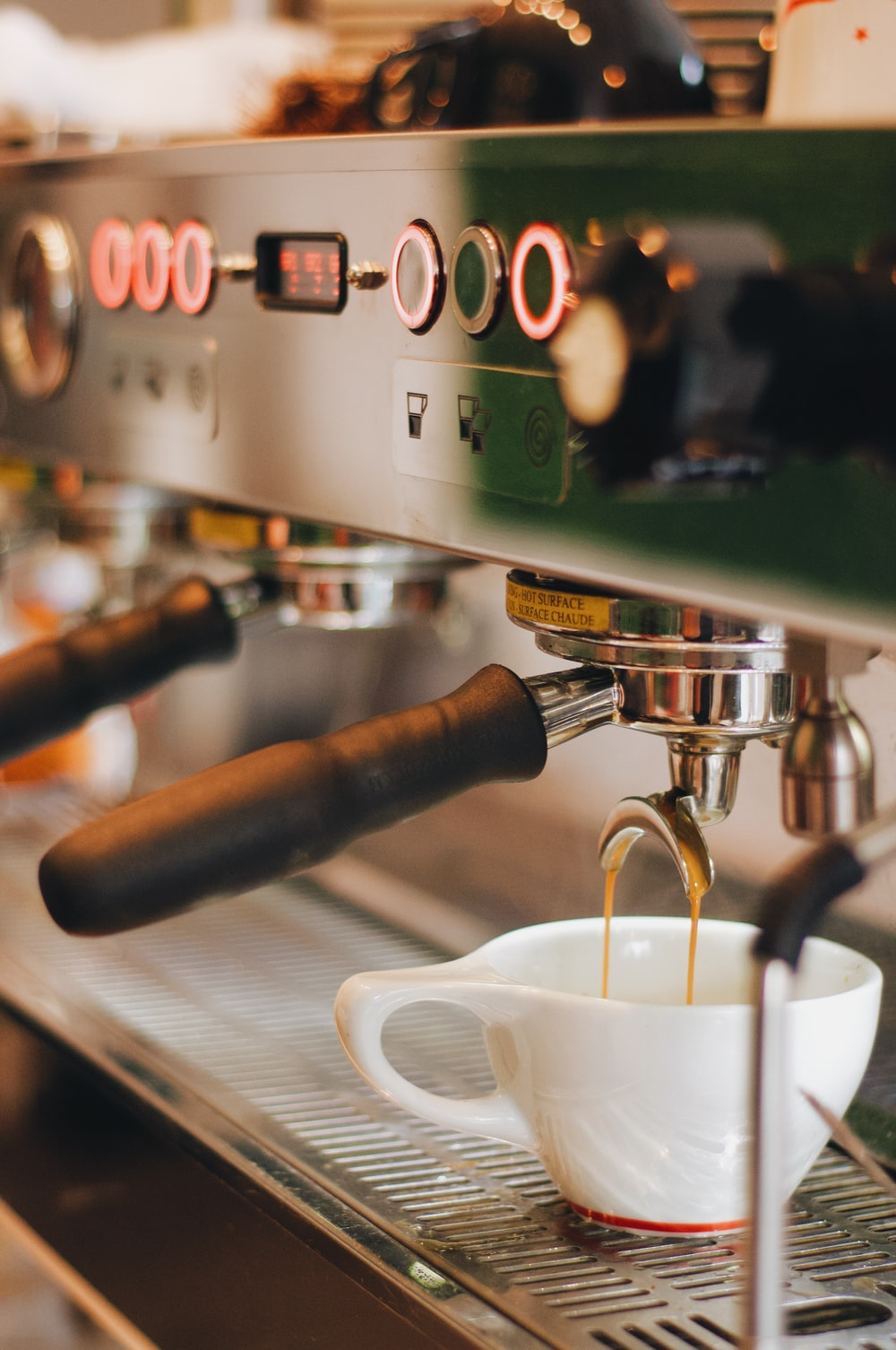 white ceramic mug on silver espresso machine