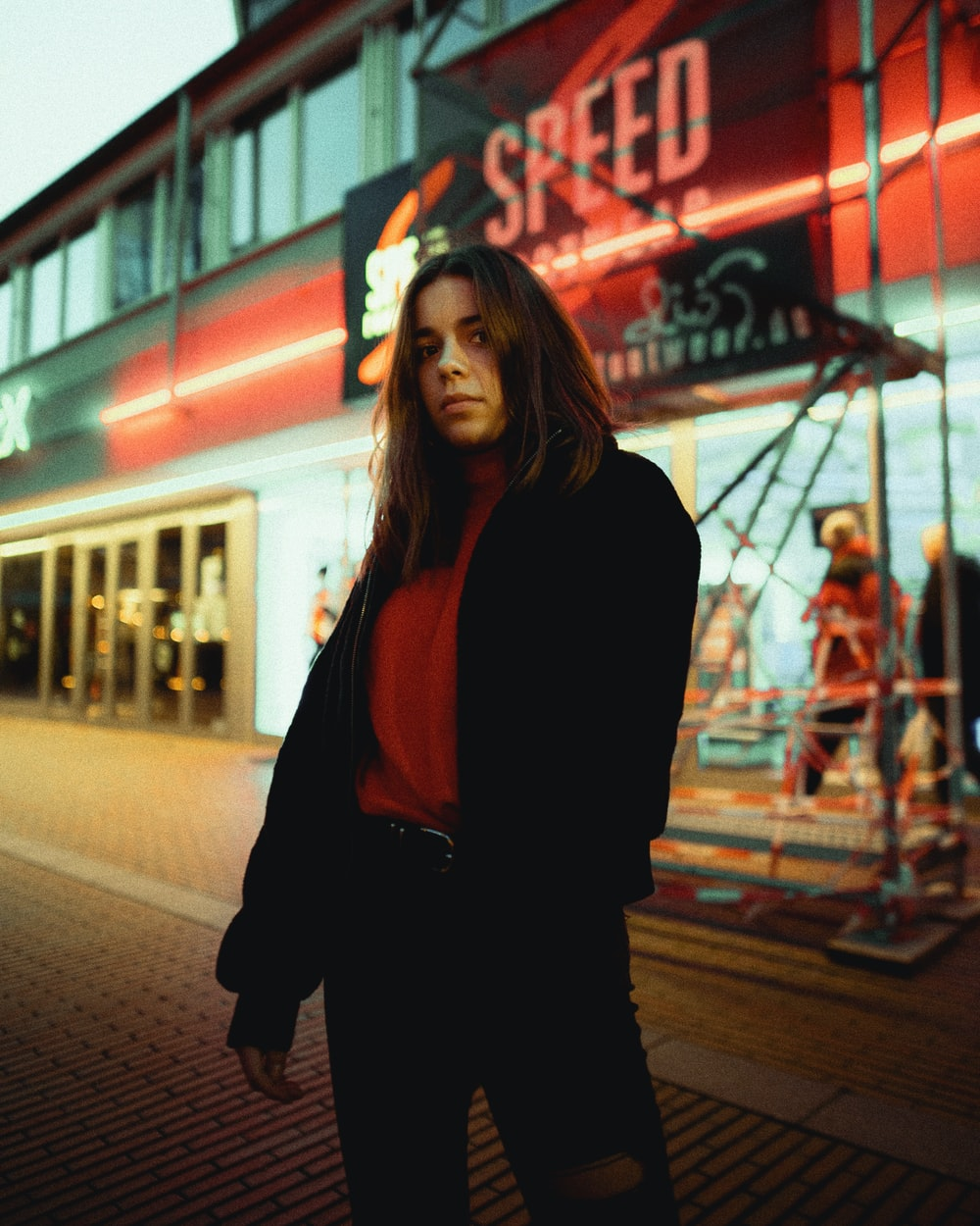 woman in black long sleeve shirt standing near red and white neon signage during night time