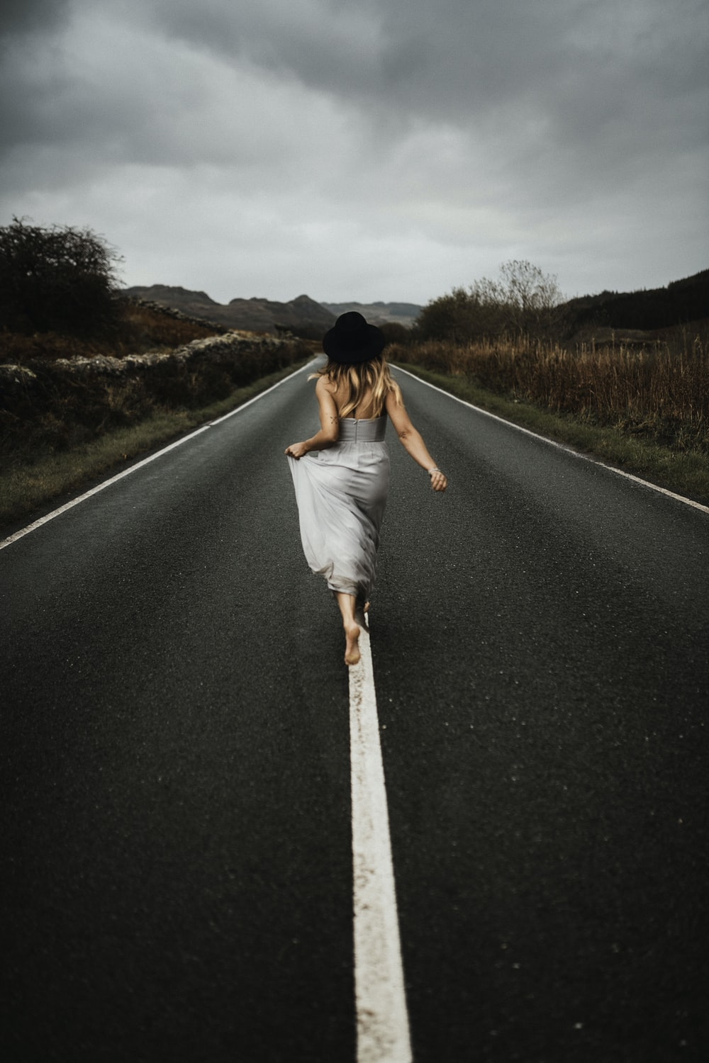 woman in white dress walking on the road