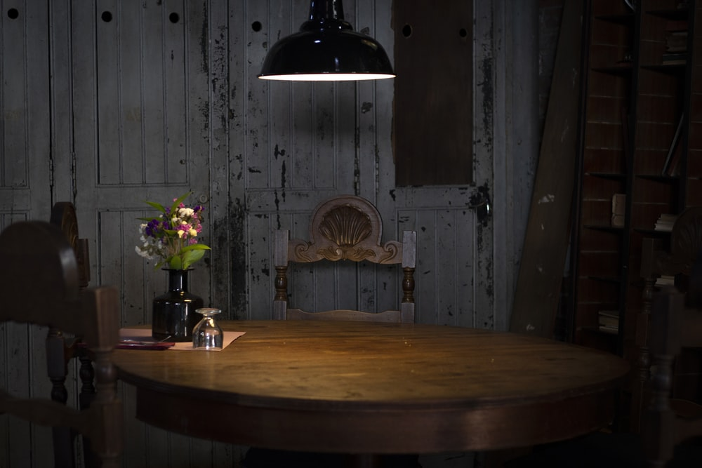 black pendant lamp turned on near brown wooden table