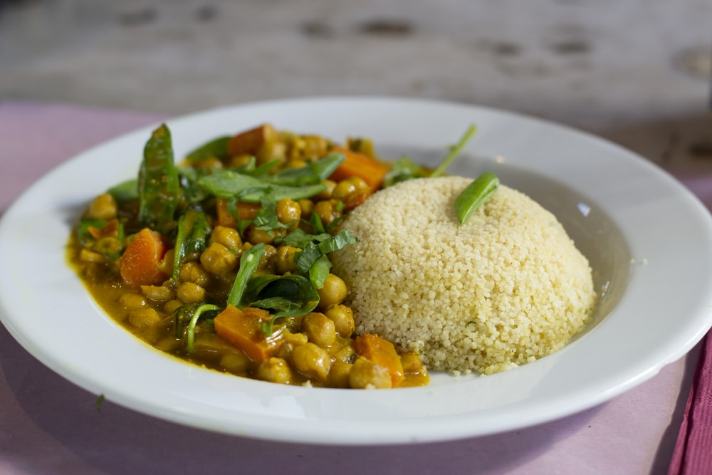 rice with green leaf vegetable on white ceramic plate
