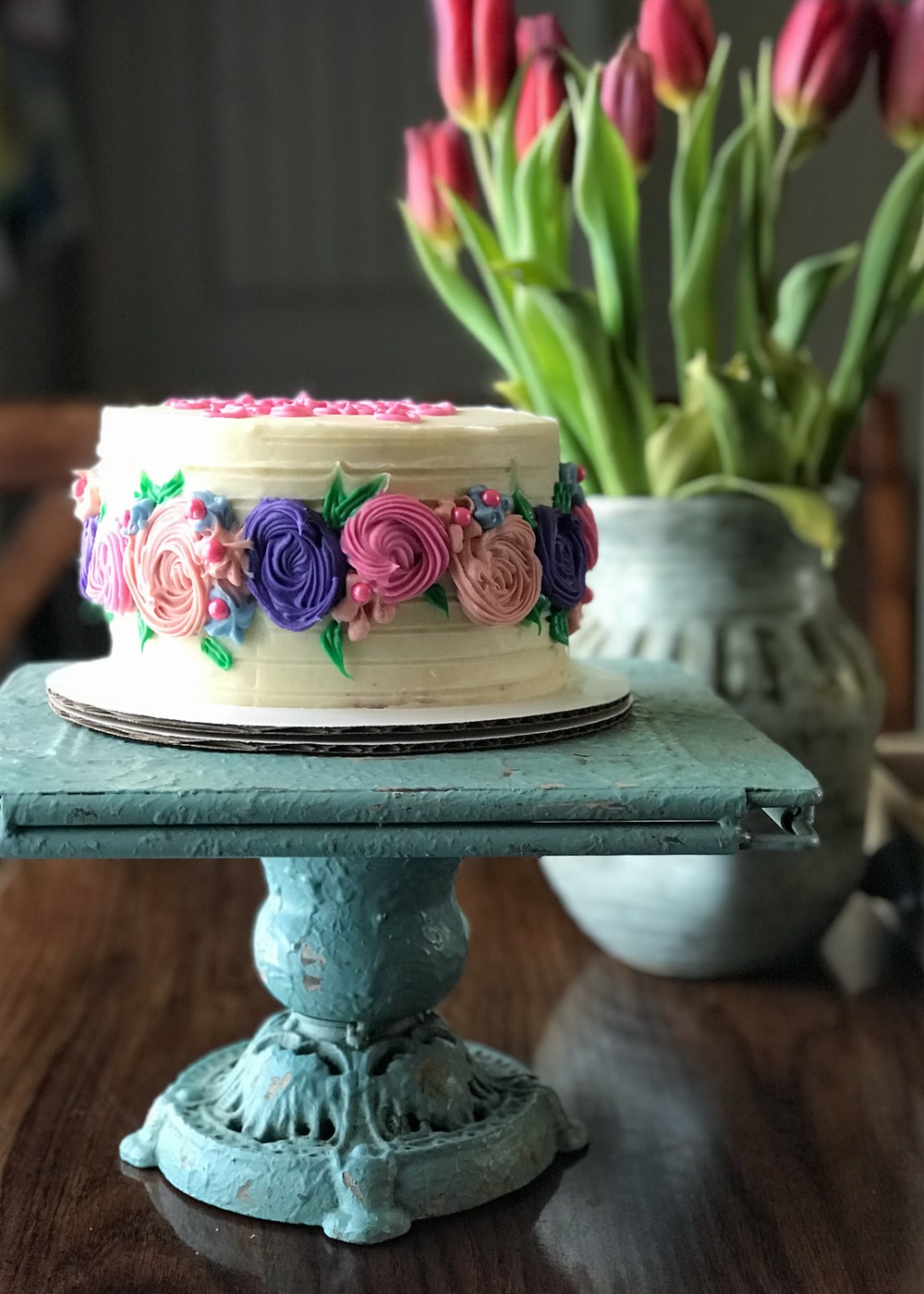 pink and white floral cake on black stand