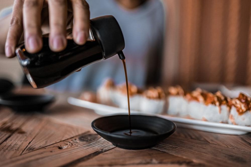 person pouring coffee on black ceramic mug