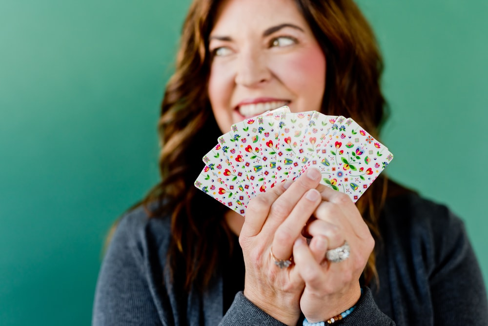 woman in gray cardigan holding white and pink floral print umbrella