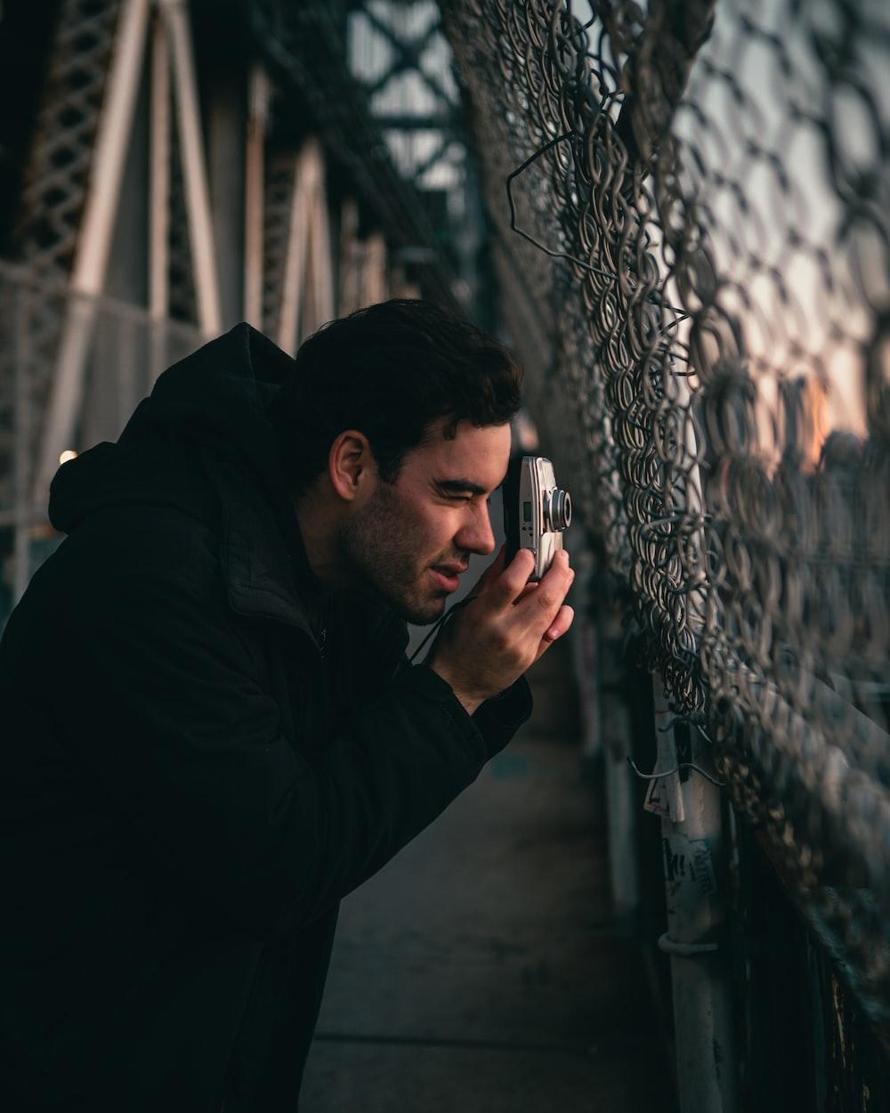 man in black jacket holding smartphone