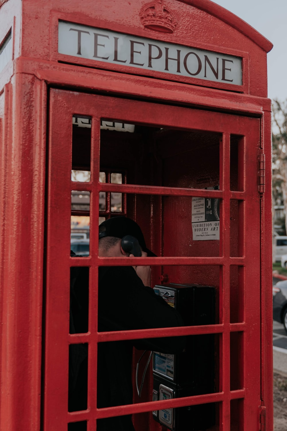 woman in black hijab and red telephone booth