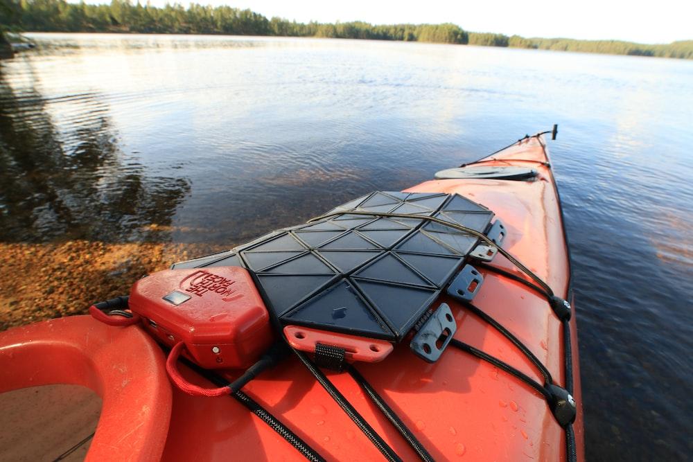 orange kayak on body of water during daytime