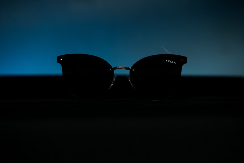 black framed sunglasses on black surface