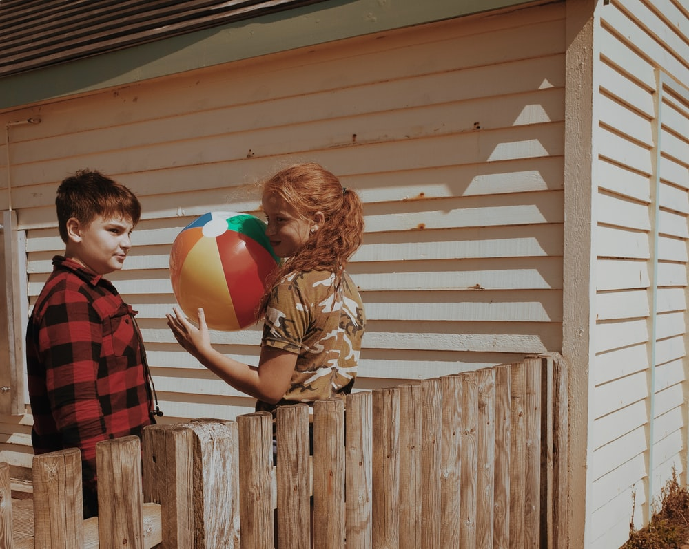 boy in brown jacket holding red yellow and blue balloons