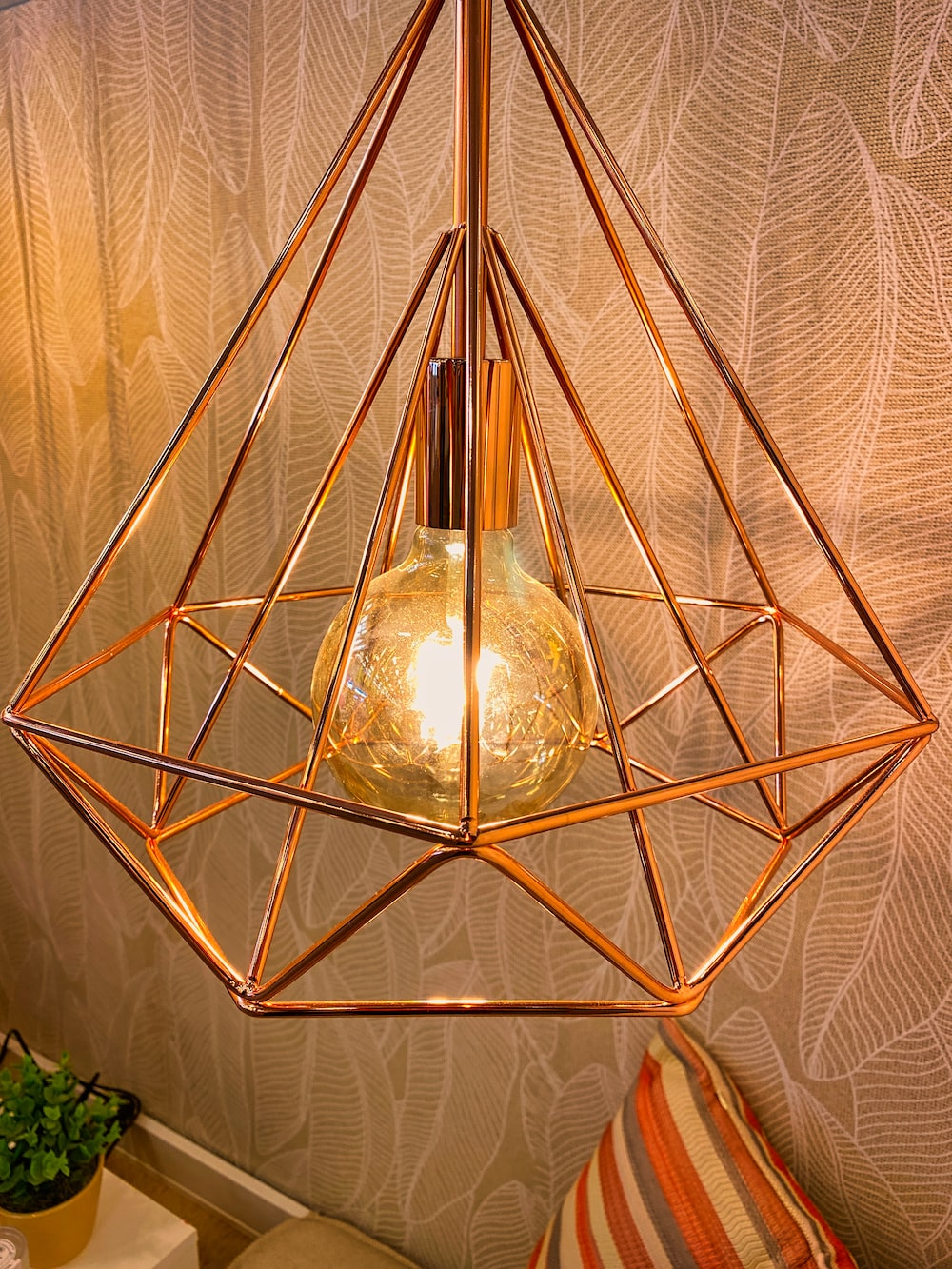 gold pendant lamp turned on near green plant