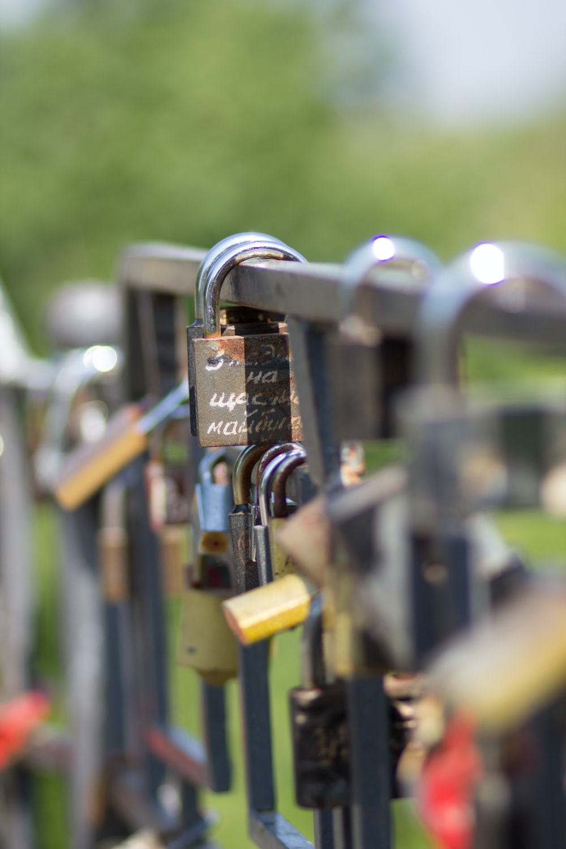 padlock on black metal fence during daytime