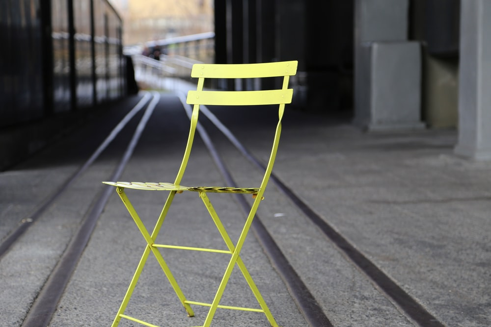 yellow metal chair on gray concrete road during daytime