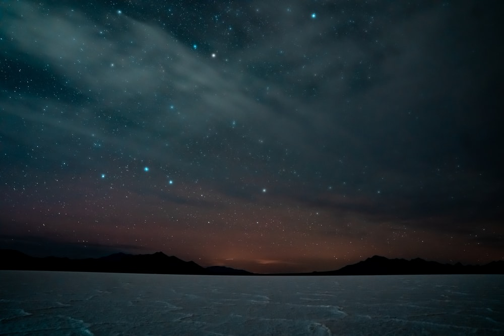 silhouette of mountain under blue sky with stars during night time