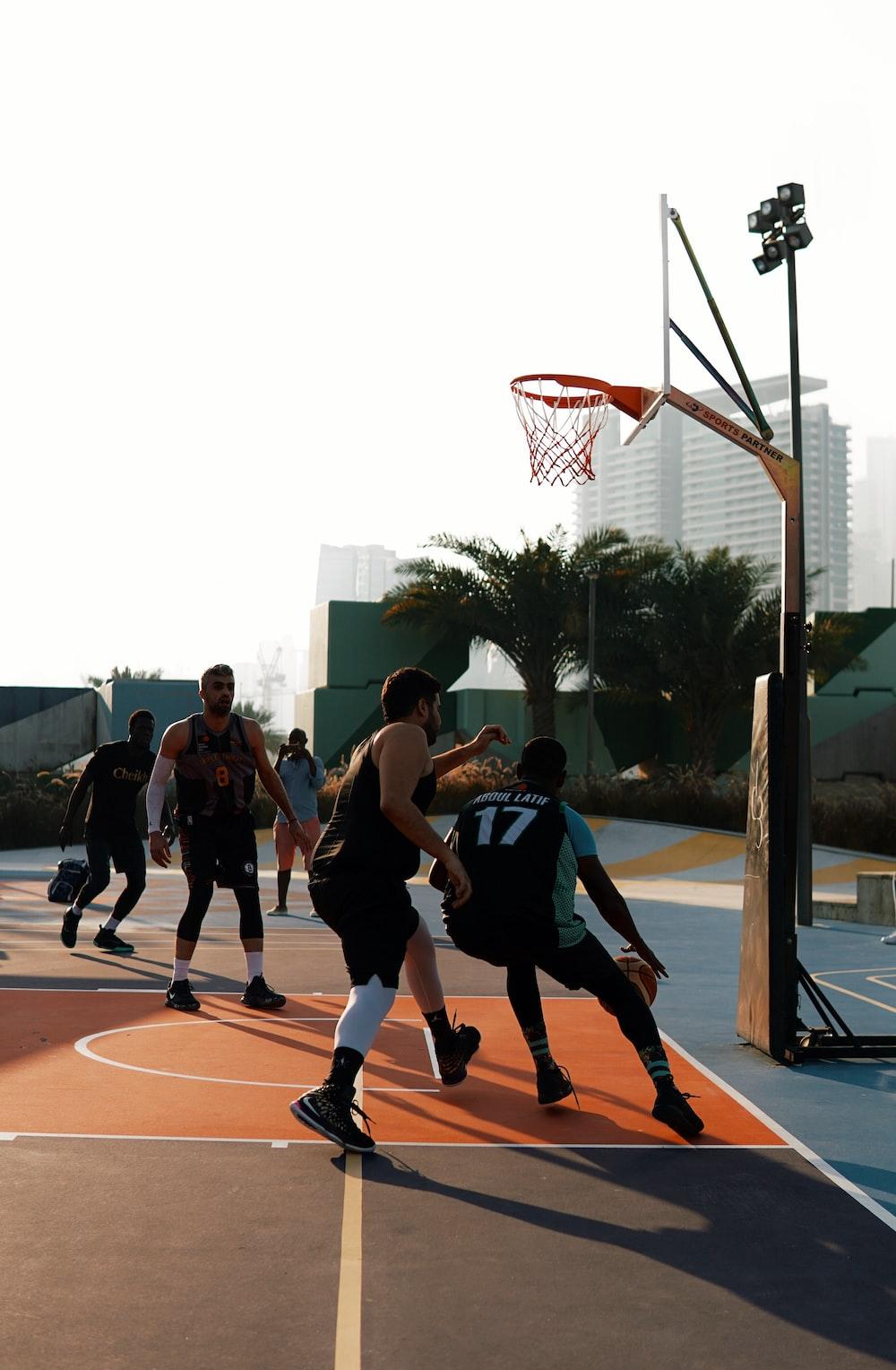people playing basketball during daytime