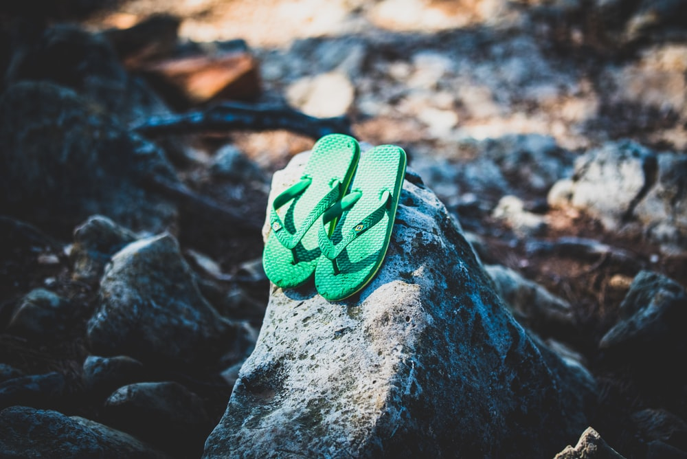 green flip flops on gray rock