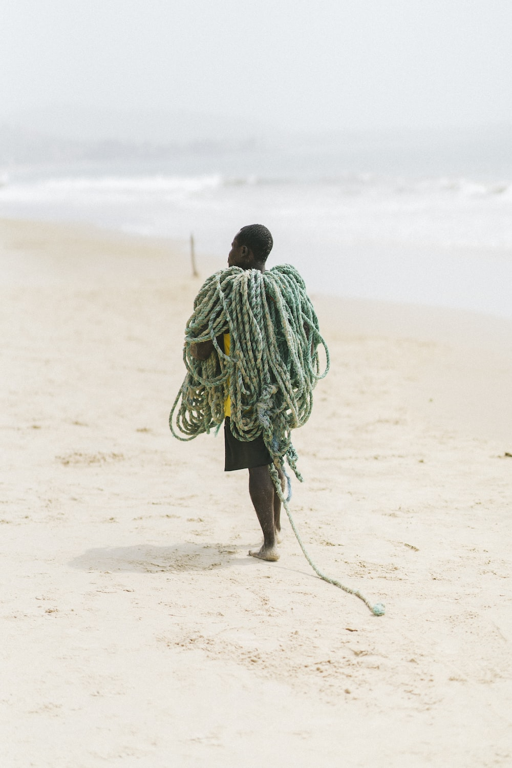 man in green and white stripe hoodie walking on brown sand during daytime