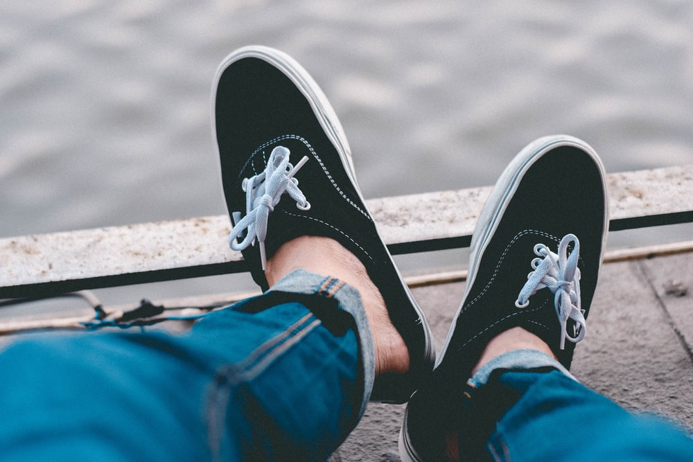 person in blue denim jeans wearing black and white sneakers