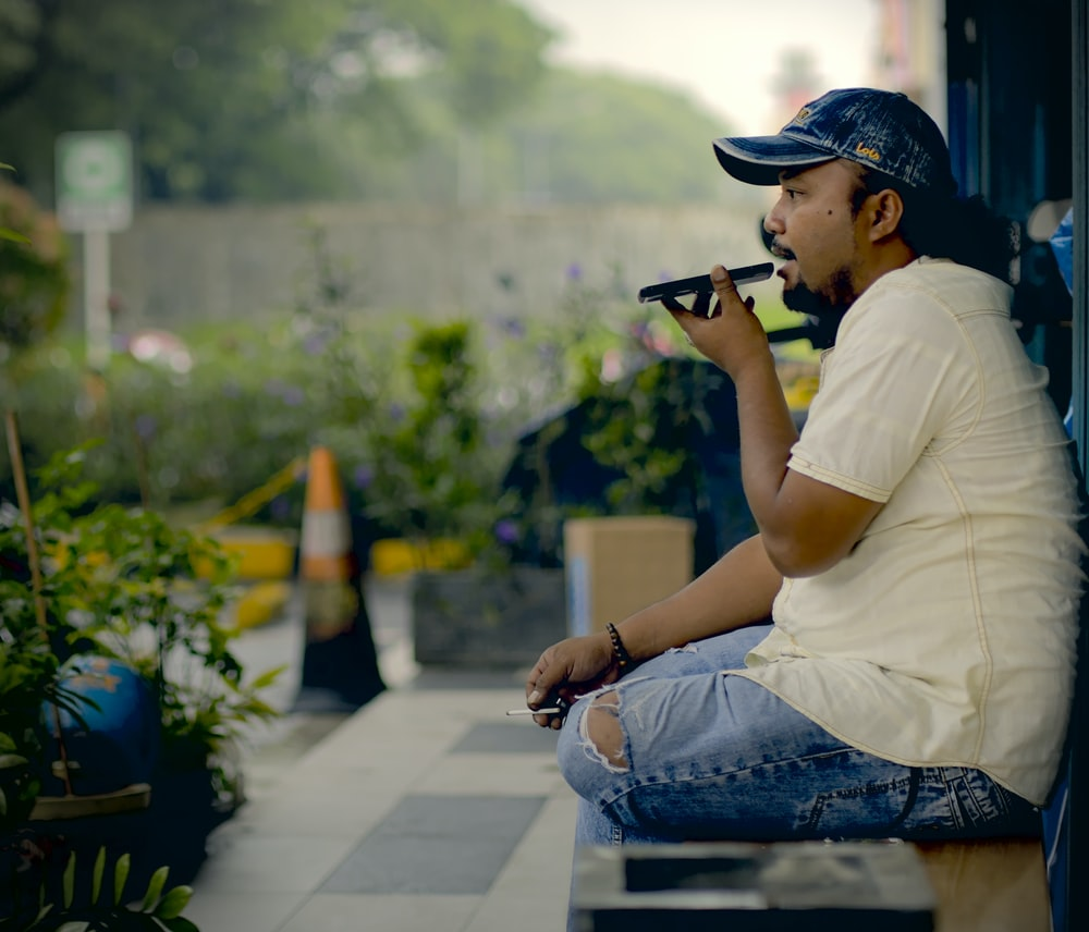 man in white t-shirt and blue denim jeans sitting on concrete bench using black dslr