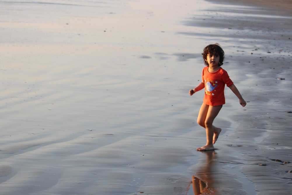 girl in pink swimsuit walking on beach during daytime