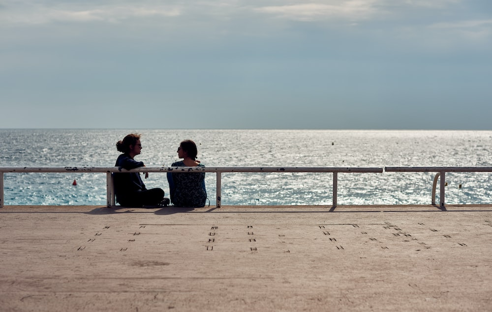 2 person sitting on bench near sea during daytime