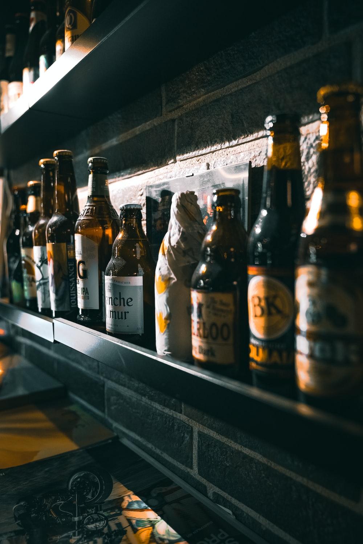 brown glass bottles on white wooden shelf