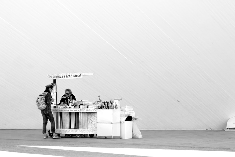 grayscale photo of people standing near table